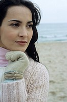 Young brownhaired Woman with Gloves and Cardigan at the Beach _ Holiday _ Temperature