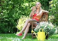 Young blond woman resting in garden