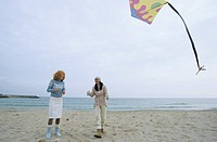 Two female Friends laughing while a Kite flies by - Friendship - Fun - Trip - Season - Beach (thumbnail)