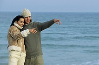 Couple at the beach pointing at something