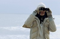 Young brownhaired Woman with woolen Hat looking through Binoculars - View - Leisure Time - Coldness... (thumbnail)