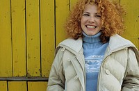 Young Woman with red curly Hair leaning against a yellow wooden Wall _ Winterly Clothing _ Season _ Facial Expression