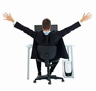 Business man with arms raised in excitement at office desk isolated on white background