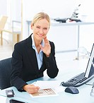 Portrait of a young smiling business woman sitting at office desk