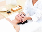 Young woman receiving facial massage at day spa