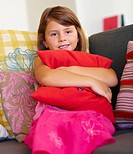 Portrait of a sweet little girl holding a pillow tightly while sitting on the couch