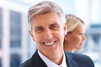 Closeup of a business man smiling, colleague in the background