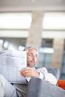 Portrait of an aged business man looking away holding a newspaper