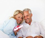 Portrait of a romantic couple in bed holding anniversary gift
