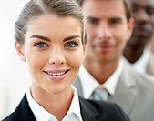 Closeup portrait of a happy young business woman with her colleagues at her back