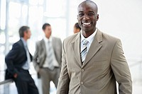 Portrait of a handsome confident African American business man smiling with his colleagues standing behind