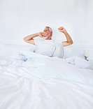 Image of an old mature man lying on the bed and yawning