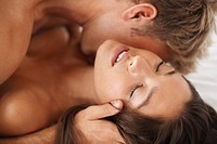 Passionate newlyweds during foreplay on the bed