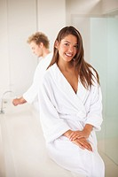 Happy woman in the bathroom with her husband at the back