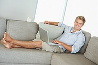 A happy smart business man relaxing on a sofa