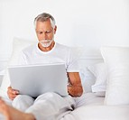 An elder senior male busy working on a laptop