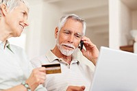 Old couple at home using the credit card to shop from the net