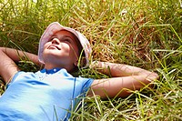 Portrait of a girl with her hands behind her head and resting on grass