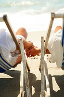 Young couple holding hands while relaxing on deck chairs