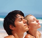 Closeup of an attractive couple meditating at the beach