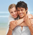 Closeup portrait of a happy young couple together on the beach