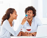 Portrait of a young woman showing her cell phone to a man who is working on the laptop