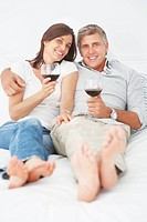 Portrait of a cute mature couple lying on their bed enjoying a glass of wine