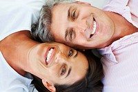 Closeup portrait of a happy mature couple lying down with their heads together