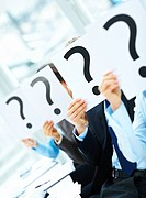 Business people holding question mark on boards in the conference room