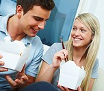 Portrait of a cute young couple eating from a takeaway container with chopsticks
