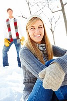 Portrait of a pretty young female sitting outside on snow with her boyfriend standing at the back