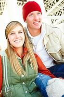 Portrait of two happy friends in winter wear sitting together