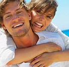 Closeup of a happy woman hugging young man at the beach
