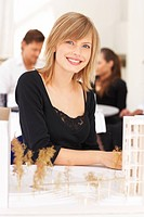 Happy pretty female architect with a model building