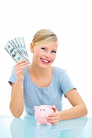 Young pretty woman with piggybank and currency over white background