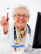 Portrait image of elderly female doctor with a vial
