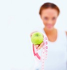 Woman showing measurement tape and fresh green apple as healthy diet