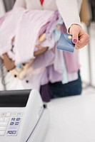 Young woman making her payments by credit card at a clothes store