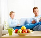 Couple using laptop and reading book with focus on fresh fruits in the foreground