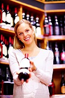 Pretty young woman holding wine bottle