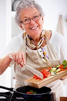 Closeup portrait of an old woman smiling and cooking food