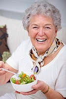 Closeup portrait of an old woman sitting and having food
