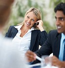 Happy young business woman speaking on the cell phone while in a meeting
