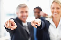 Blur image of happy business people pointing towards the viewer