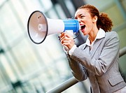 Beautiful African American business woman yelling into a bullhorn