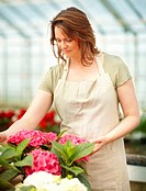 Happy young female florist working while at a greenhouse