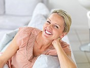 Portrait of a happy mature woman laughing while sitting on the couch at home