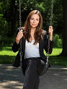 Young attractive businesswoman sitting on a swing in a park