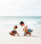 Happy father and son on a beach vacation, boy playing with a conch shell