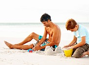 Happy father and son making sand castles, playing at the sea shore